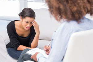 Woman crying on sofa during therapy session while therapist is t