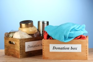 Donation boxes with clothing and food on blue background close-u
