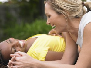 Two cheerful multiethnic women lying outdoors and laughing