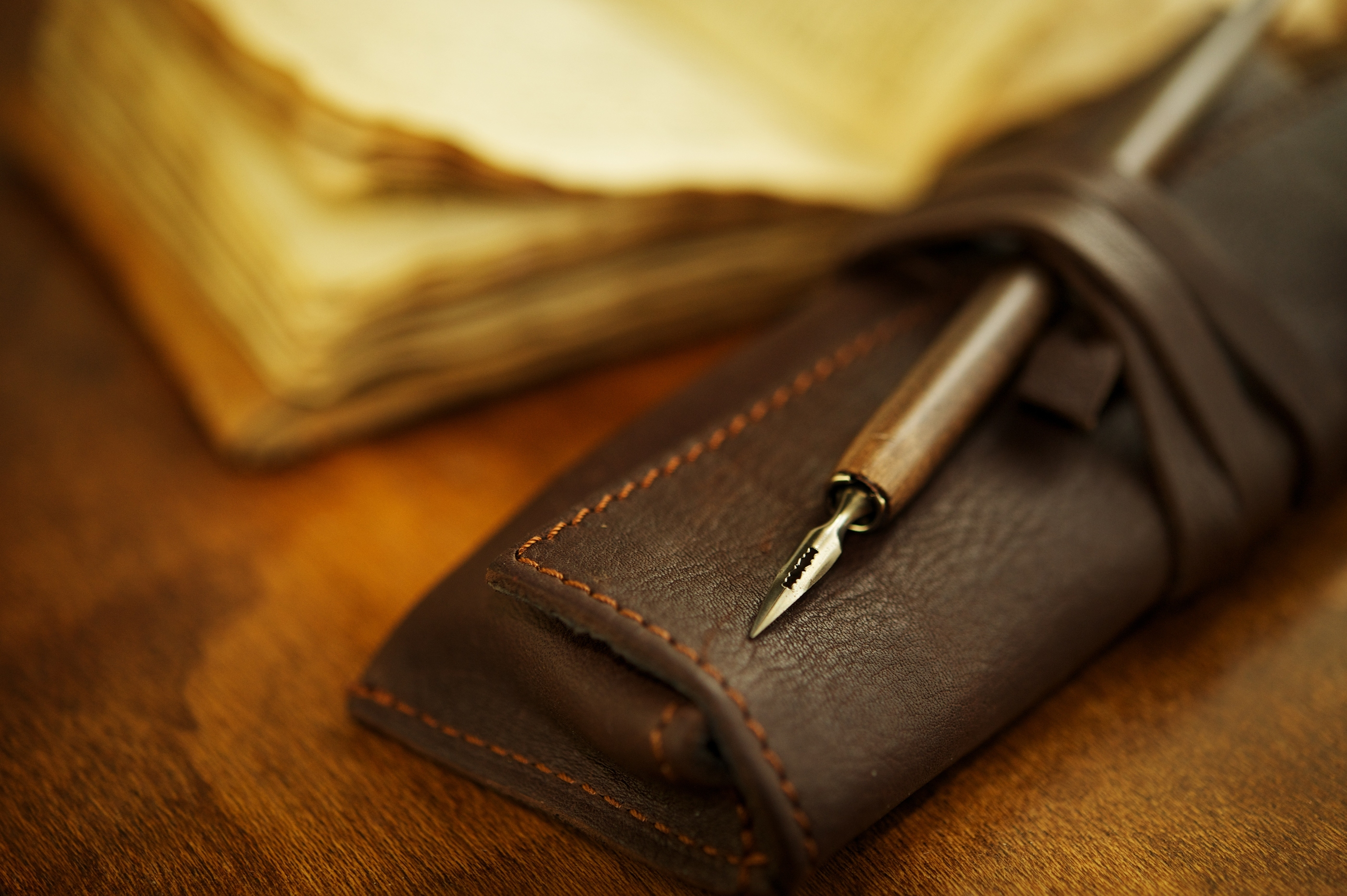 Quill pen near a vintage book.