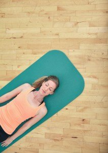 Top view of woman relaxing on yoga mat with copy space. Fitness female lying on exercise mat at gym.
