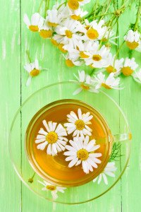 Herbal chamomile tea and flowers on green table top view