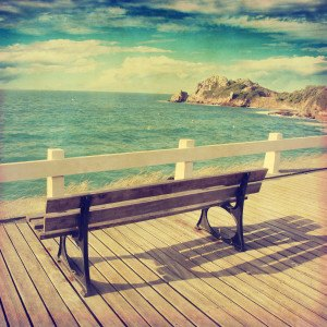 Image of bench near the ocean in vintage style.
