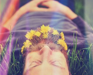 a sleeping hipster lying in tall grass with dandelions in his ep