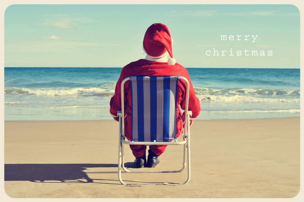 a picture of santa claus sitting in a beach chair on the beach a