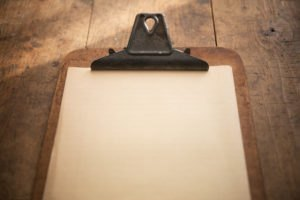 An vintage clipboard on a old wooden table, with blank old white
