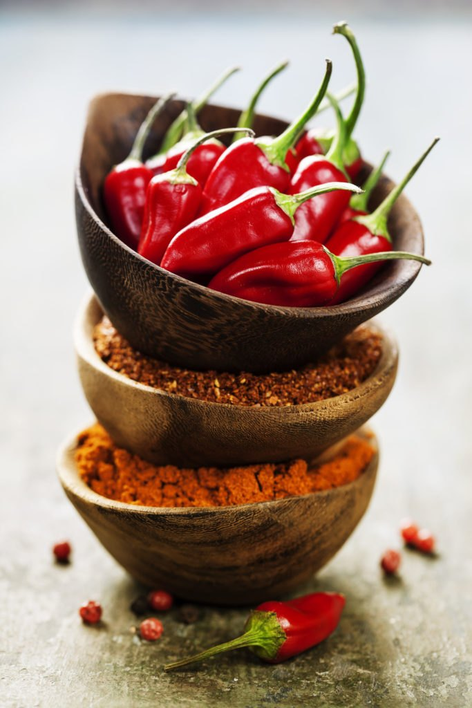 Red Hot Chili Peppers with herbs and spices over wooden backgrou